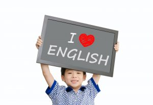 "Kid holding up ""I love English"" sign"